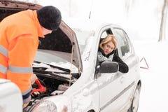 Man repairing woman's car snow assistance winter. Broken tools mechanic Stock Images