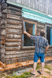 Man repairing a wooden house Stock Image