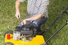 Man repairing yellow lawn mower Stock Images