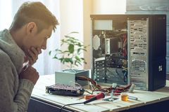 Man repairman is trying to fix using the tools on the computer that is on a workplace in the office. The concept of service electronics and computers Royalty Free Stock Photos