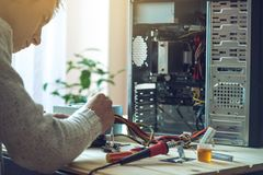 Man repairman is trying to fix using the tools on the computer that is on a workplace in the office. The concept of service electronics and computers Stock Images