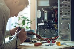 Man repairman is trying to fix using the tools on the computer that is on a workplace in the office. The concept of service electronics and computers Royalty Free Stock Photography
