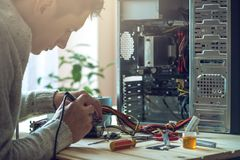 Man repairman is trying to fix using the tools on the computer that is on a workplace in the office. The concept of service electronics and computers Royalty Free Stock Images