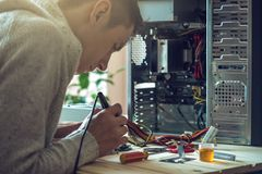 Man repairman is trying to fix using the tools on the computer that is on a workplace in the office. The concept of service electronics and computers Stock Image