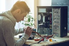 Man repairman is trying to fix using the tools on the computer that is on a workplace in the office. The concept of service electronics and computers Stock Photography