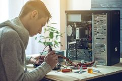 Man repairman is trying to fix using the tools on the computer that is on a workplace in the office. The concept of service electronics and computers Stock Photo