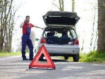 A man repairs a car on the road. Vehicle breakdown red triangle road Stock Photography