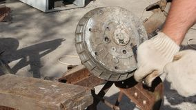 A man repairs a car trailer. Removing the drum from the hub stock video
