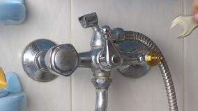 The man repairs the faucet in the bathroom, changes the axle, close-up.  stock video