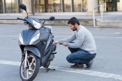 Man repairs a scooter. Man screwing a scooter outside Royalty Free Stock Photo