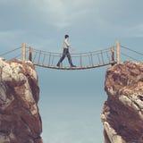Man repet som passerar över en bro inställd mellan berg Arkivbild