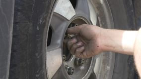 Man replaces tire on a roadside. Replacing punctured tire on the side of a road, male hands tightening screws on a wheel stock footage
