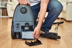 Man replacing an air filter in vacuum cleaner at home. Royalty Free Stock Image