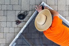 Man replacing damaged wire mesh on a screen door. Lying on the paving on an exterior patio viewed from above looking down on him kneeling stock photos