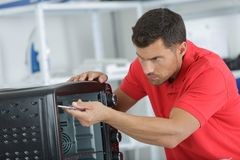 Man replacing filter in microwave in kitchen. Man replacing the filter in a microwave in the kitchen royalty free stock photography