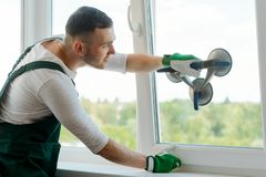 Man is replacing glass in window. Professional repairman is putting a pane into the sash using a vacuum lifter royalty free stock photo