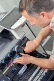 Man replacing ink in printer. Accessory royalty free stock photos
