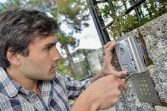 Man replacing intercom system Stock Photos