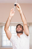 Man replacing the light bulb Stock Photography