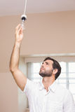 Man replacing the light bulb Stock Images