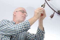 Man replacing the light bulb at home Royalty Free Stock Photography