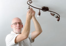 Man replacing the light bulb at home Stock Image