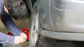 Replacing nuts on an old tire. Man replacing nuts on tire stock footage