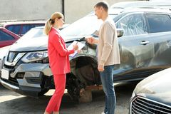 Man reporting and insurance agent filling claim form. Near broken car outdoors royalty free stock photos