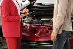 Man reporting and insurance agent with tablet filling claim form near broken car. After accident royalty free stock photo