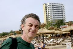 Man at resort. An elderly man squints in the afternoon sun, posing for a photo on a beach resort Stock Photos