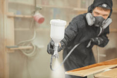 Man in respirator mask painting wooden planks at workshop. Male applicate paints and varnishes. Pneumatic spraying on wooden timber with spray paint gun Royalty Free Stock Images