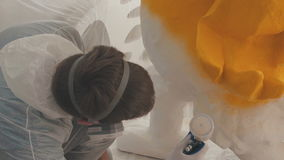 Man in respirator protective mask applies a paint using a nebulizer. The man paints a voluminous figure made of expanded polystyrene. The process of coloring a stock footage
