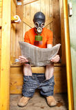 Man in respirator reading newspaper in wooden village WC Stock Image