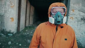 A man in a respirator and in a special overalls comes out of a concrete shelter