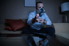 Man in respirator watching TV Stock Images