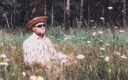 Man Rest On The Forest Lawn. Bearded man in a straw hat and sunglasses rest among flowers on the forest lawn at sunny day. Selective focus, vintage film filter Stock Photography