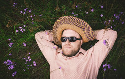 Man Rest On The Grass And Bellflowers. Bearded man in a straw hat and sunglasses rest on the grass among the blue bellflowers. Closeup, space for copy, vintage Royalty Free Stock Images