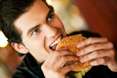 Man in restaurant eating hamburger Royalty Free Stock Image
