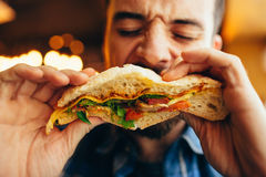 Man in a restaurant eating a hamburger Royalty Free Stock Images