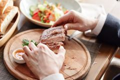The man in the restaurant with a knife cuts grilled pork ribs. Serving on a wooden Board. The man in the restaurant with a knife cuts grilled pork ribs. Serving Royalty Free Stock Image