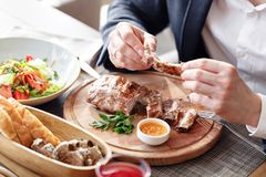 The man in the restaurant with a knife cuts grilled pork ribs. Serving on a wooden Board. The man in the restaurant with a knife cuts grilled pork ribs. Serving Royalty Free Stock Photography