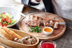 The man in the restaurant with a knife cuts grilled pork ribs. Serving on a wooden Board. The man in the restaurant with a knife cuts grilled pork ribs. Serving Stock Photos