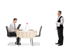 Man at a restaurant table reading a menu. Young men seated at a restaurant table reading a menu and a waiter waiting to be called isolated on white background Stock Photo