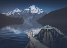 Man resting on a alpine lake. Instagram stylization. Man resting in a wooden boat on a alpine lake in front of great caucasian mountain Tetnuldi. Night picture Stock Photo
