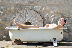 Man resting in the bathtub. Man resting in the outdoor bathtub royalty free stock image