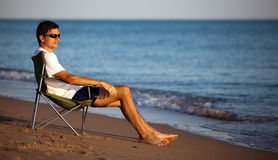 Man resting on the beach. Young man resting in the chaise longue on the beach stock photos