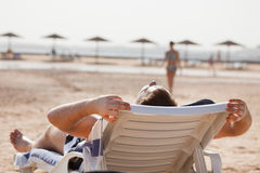 Man resting in beach chair Stock Photography
