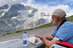 Man resting on a beach and eating breakfast. hiking in grossglo Royalty Free Stock Images