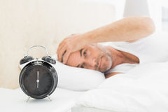 Man resting in bed with alarm clock in foreground Royalty Free Stock Photos