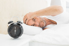 Man resting in bed with alarm clock in foreground. Mature man resting in bed with alarm clock in foreground at bedroom Stock Image